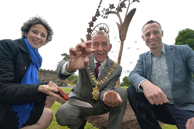 Suzanne Lyle, Head of Visual Arts with the Arts Council of Northern Ireland, and Lord Mayor of Belfast, Councillor Arder Carson, join artist Alex Pentek to put the finishing touches to wildflower planting around the new Forget Me Not sculpture
